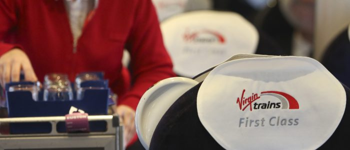 An employee serves refreshments from a snack trolley in the first class compartment of a West Coast train, operated by Virgin Trains, as it travels from London to Milton Keynes, U.K., on Thursday, Nov. 27, 2014. Virgin Trains and partner Stagecoach Group Plc were chosen to run the London-Edinburgh rail route, fending off rival bids from FirstGroup Plc and Eurostar International Ltd. and delivering a boost for Richard Branson a month after the fatal crash involving his space venture. Photographer: Chris Ratcliffe/Bloomberg via Getty Images
